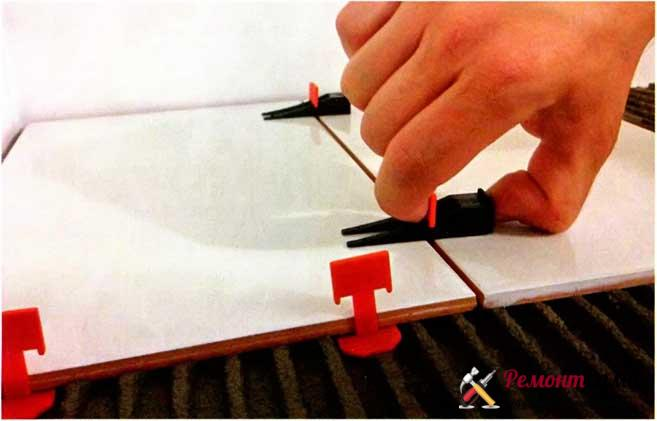 После укладки соседних плиток в зажим с усилием вставляют клин, который выравнивает положение плиток относительно друг друга.