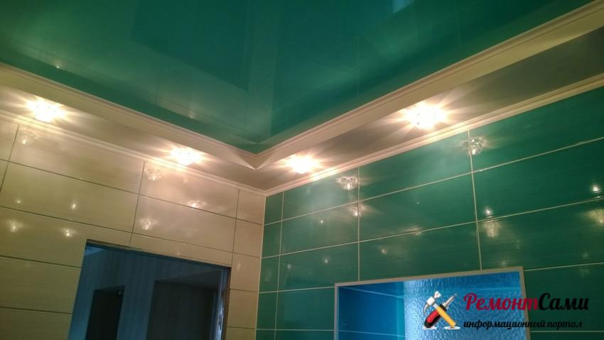 Зеленый натяжной потолок в ванной гармонирует по цвету с плиткой